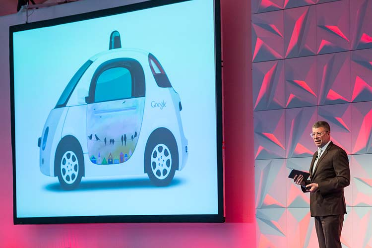 Conference speaker giving presentation on stage with image of Google car