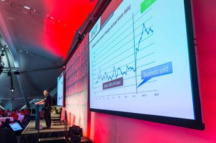 Conference speaker at podium with graph on screen