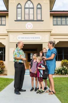 School teacher talking to parent and her children in front of school building