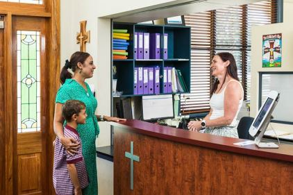 Parent and child talking to school reception in catholic school