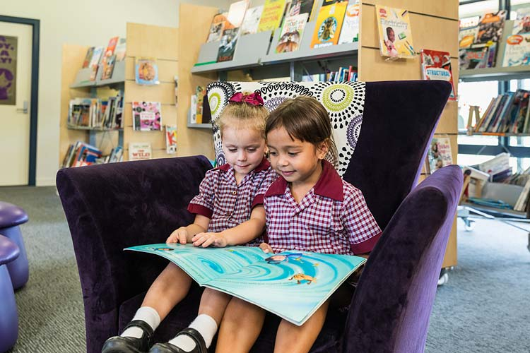 Two young school children sitting in library chair sharing a book