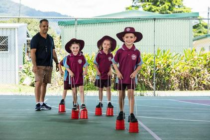 Group of school kids playing on tin-can stilts with teacher watching on