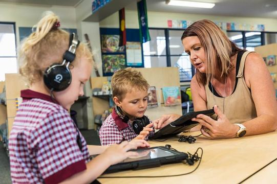 Teacher assisting young student learning on an iPad