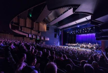 Crowds watching an orchestral performance on stage at the Cairns Performing Arts Centre