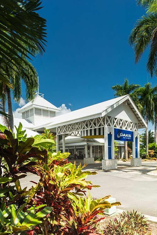 View through foliage to resort facade in Port Douglas