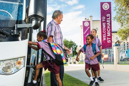 Young indigenous students boarding a bus in front of school