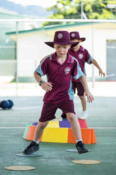 Young school students doing agility exercise in physical education class