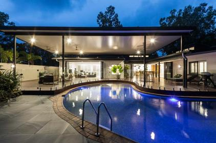 Pool and outdoor entertaining area of residential home illuminated at twilight