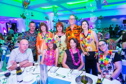 Group of delegates in tropical dress at conference dinner