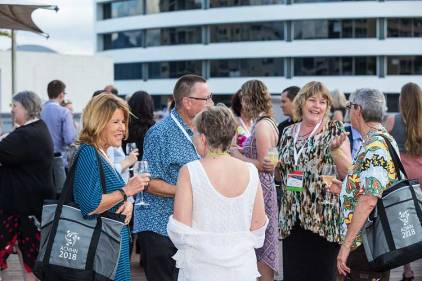 Group of conference delegates enjoying a drink at a networking function