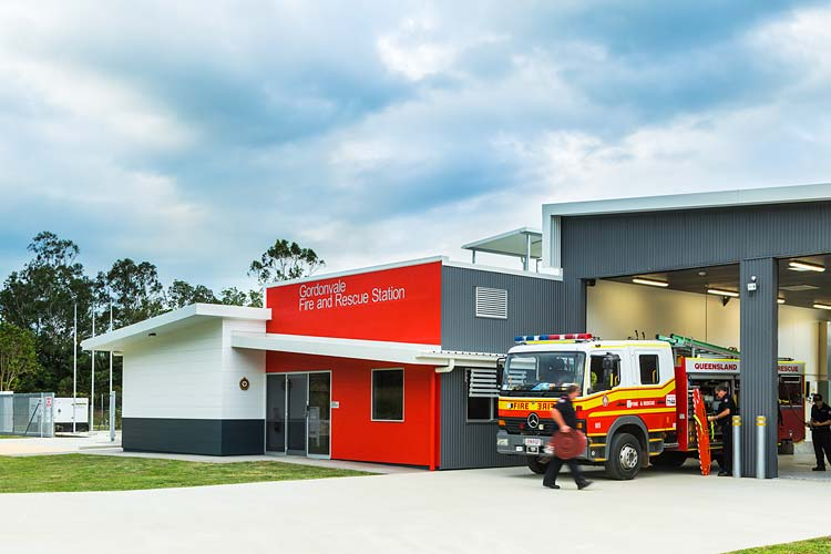 Exterior of the Gordonvale Fire Station building with staff readying fire truck equipment