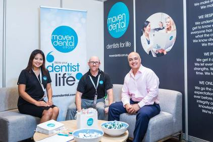 Dental suppliers sitting in booth at conference tradeshow