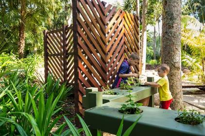 Kids touching and feeling herbs in an outdoor sensory playground