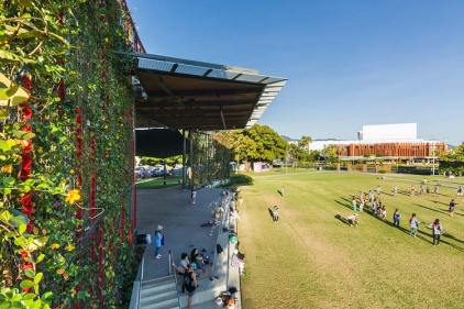 View along a flowering trellis with a group enjoying the parklands lawn