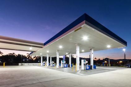 Fuel pump forecourt of service station illuminated at twilight
