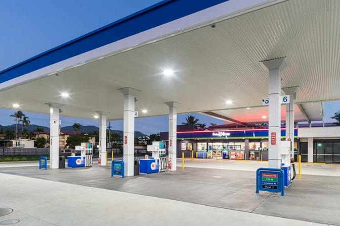 Fuel pump forecourt and convenience store of service station illuminated at twilight