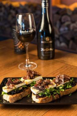 An entree dish of Brie & Biltong Bruschetta with a glass of red wine