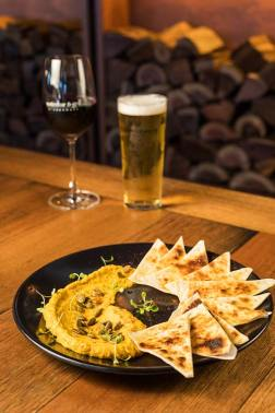 An entree dish of pumpkin hummus with pistachios, pepitas and flatbread on a restaurant table