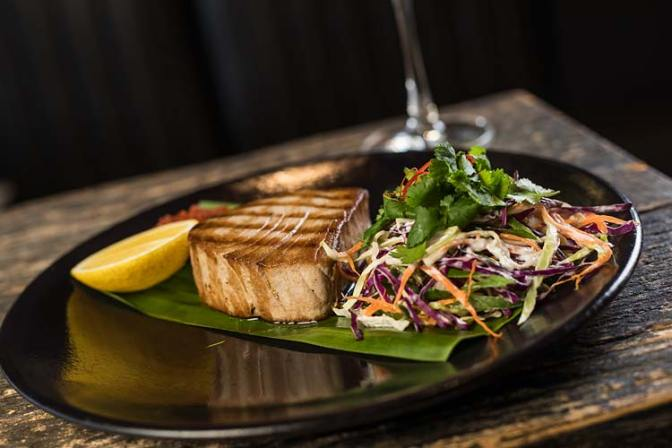 A restaurant dish of grilled swordfish and salad