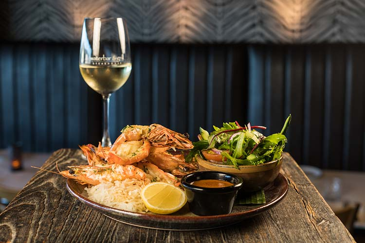 A restaurant dish of prawns, salad and glass of white wine