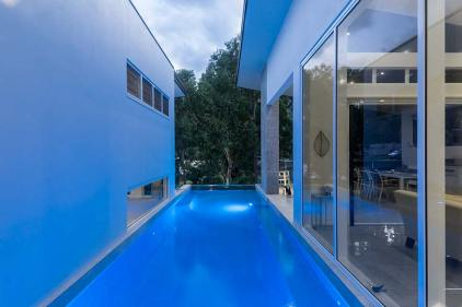 View of residential home lap pool illuminated at twilight