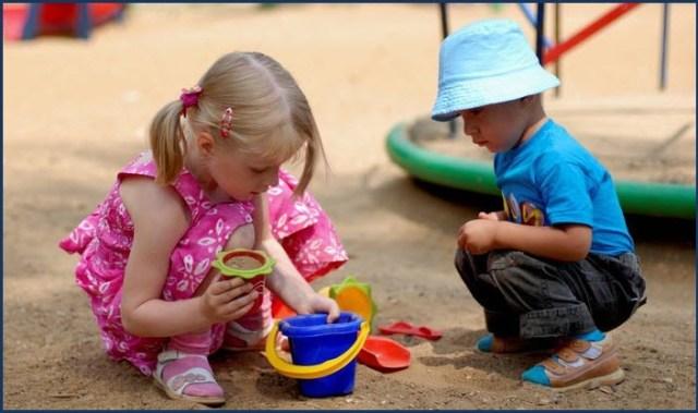 Девочка и мальчик играют в песочнице
