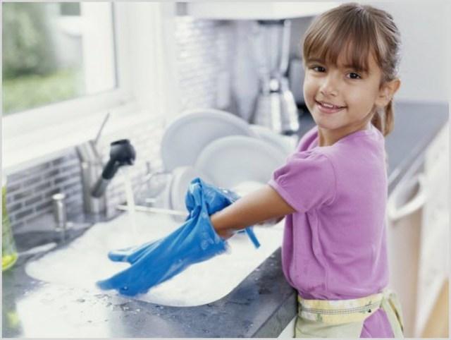 Девчушка с удовольствием моет посуду