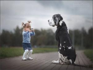 Девочка фотографирует пса