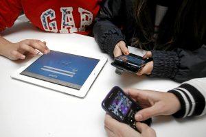 Un grupo de niños manejando teléfonosmóviles y 'tablets' con las que tienen acceso a las redes sociales y programas de mensajería instantánea. Adolescentes. Horizontal