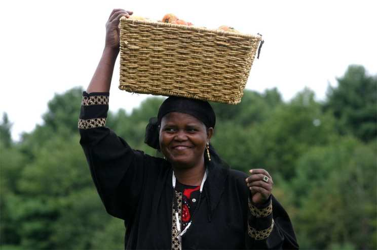 Troy R. Bennett / The Times Record August 29, 2006 Habibo Noor brings a basket of tomatos in from the field in Lisbon Tuesday. Noor, originally from Somalia, leases land with the New American Sustainable Agriculture Project to grow produce to sell at farmer's markets.