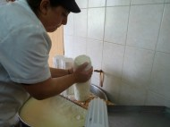 Koula squeezing out the liquid to make cheese