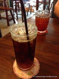 A strong Americano in a blue sugar rimmed glass and a iced tea.