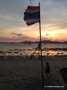 Sunset on Cape Panwa beach with the Thai flag and my favorite little girl.