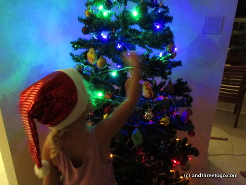 My little santa girl putting the final touches on the tree.