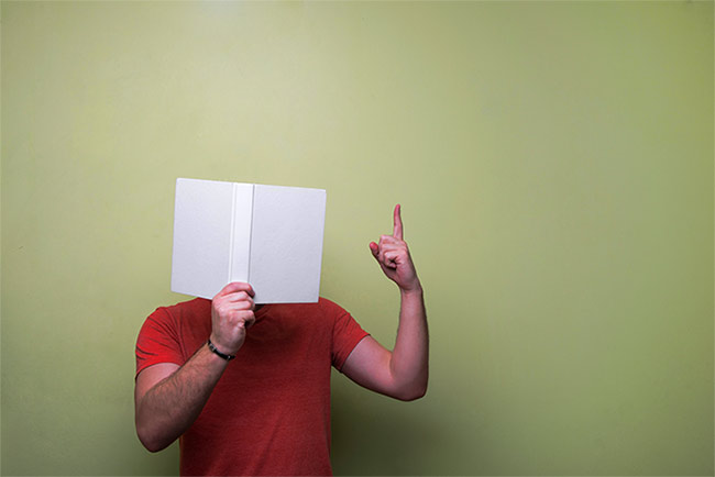 Man with head in book and finger up