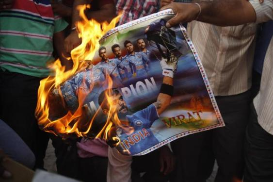 Indian fans burn a poster of Indian cricket team members as they react to India's defeat in the ICC cricket world cup semi-final match against Australia