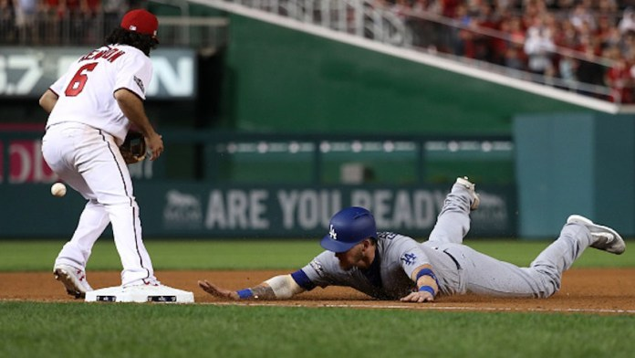 WASHINGTON, DC - OCTOBER 7: Yasmani Grandal #9 of the Los Angeles Dodgers slides safely into third base against Anthony Rendon #6 of the Washington Nationals during the ninth inning in game one of the National League Division Series at Nationals Park on October 7, 2016 in Washington, DC. (Photo by Rob Carr/Getty Images)