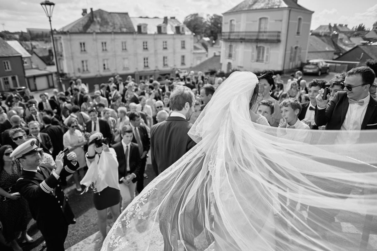 courbes esthétiques du voile de la mariée à la sortie de l'église de craon