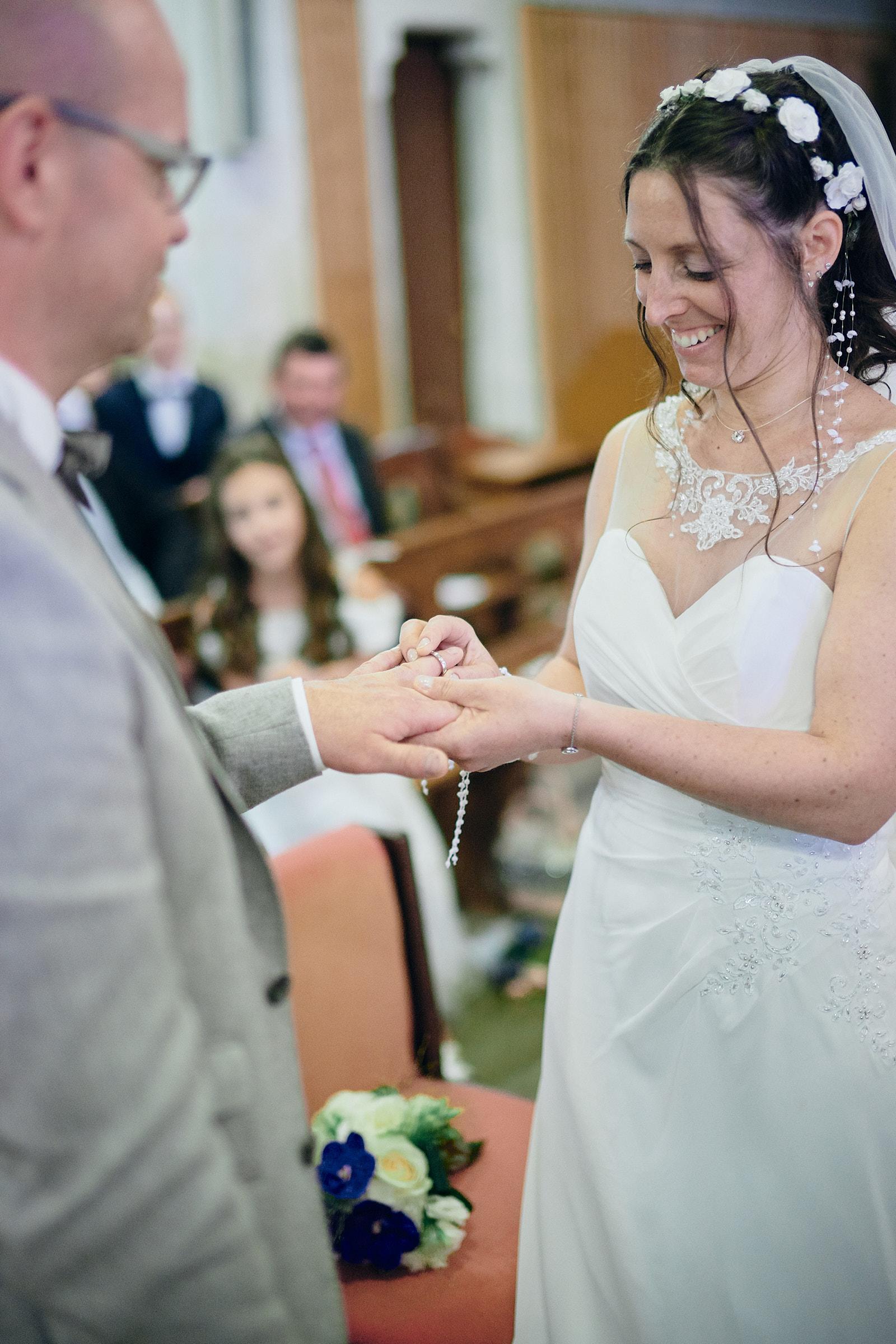 la mariée passe l'alliance au doigt du marié