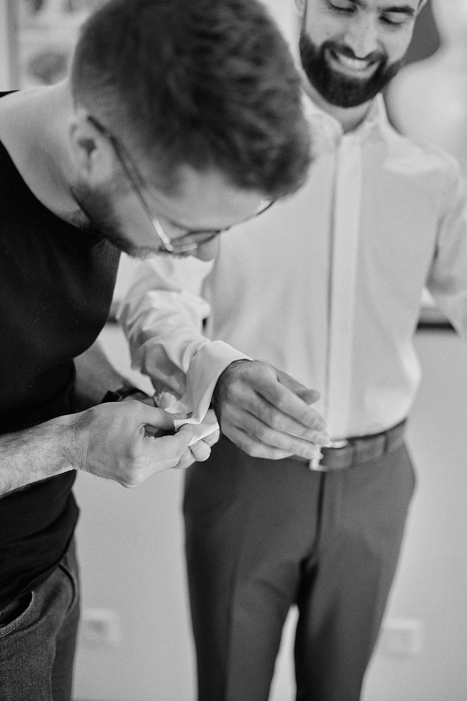 un des témoins aide le marié à mettre ses boutons de manchette