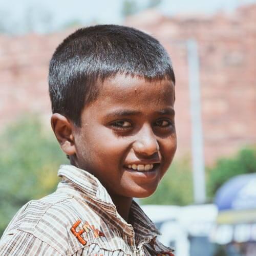 Bettlerjunge in Indien lacht