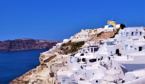 Cascade of Cycladic White-washed cave houses in Oia, Santorini