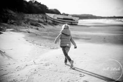 Mädchen läuft am Strand auf ein Boot zu
