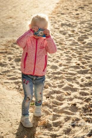 kleines Blondes Mädchen am Ostseestrand hält sich eine Kamera vors Gesicht