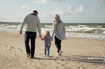 Familie geht am Strand spazieren Mutter und Vater halten die Hände des kleinen Mädchens