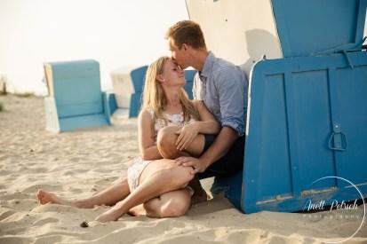 Paarshooting am Strand von Usedom Mann küsst einer Frau auf die Stirn sie sitzen hinter einem Strandkorb