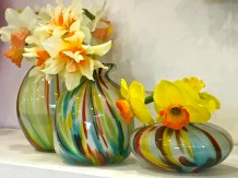 """These hand-blown vases perfectly offset the ruffled petals and cheery color of daffodils. Their scientific name """"Narcissus"""" comes from the Greek legend of a young man by the same name, who fell so in love with his own gorgeous reflection while gazing into a river that he tumbled into the water and drowned. The flower was said to have sprung up along the bank where Narcissus sat admiring himself. (Notice that the head of a daffodil is bent downward toward the ground, as if looking for its own reflection.)"""