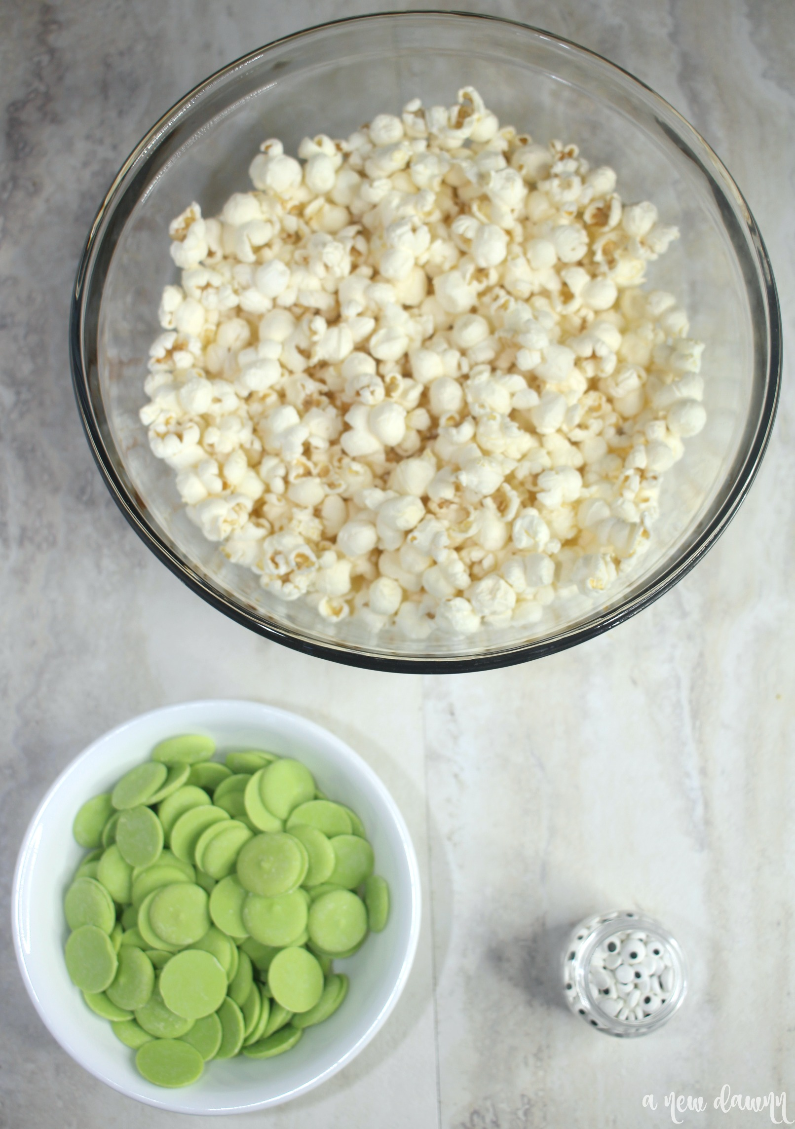 a bowl of popcorn and green candy metls