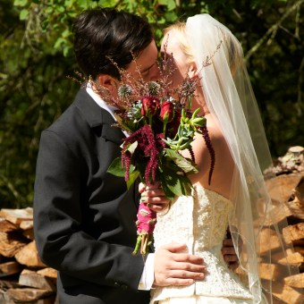 a groom & bride kissing with bouquet held in front of by the bride