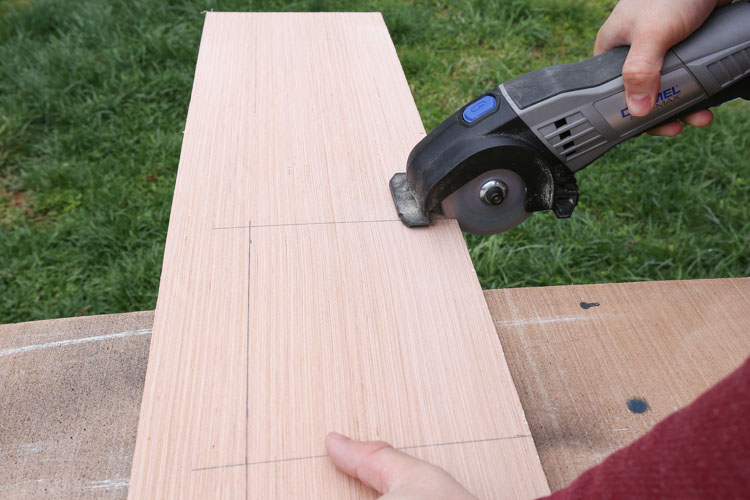 A dremel cutting an opening out of shiplap board for ceiling vent